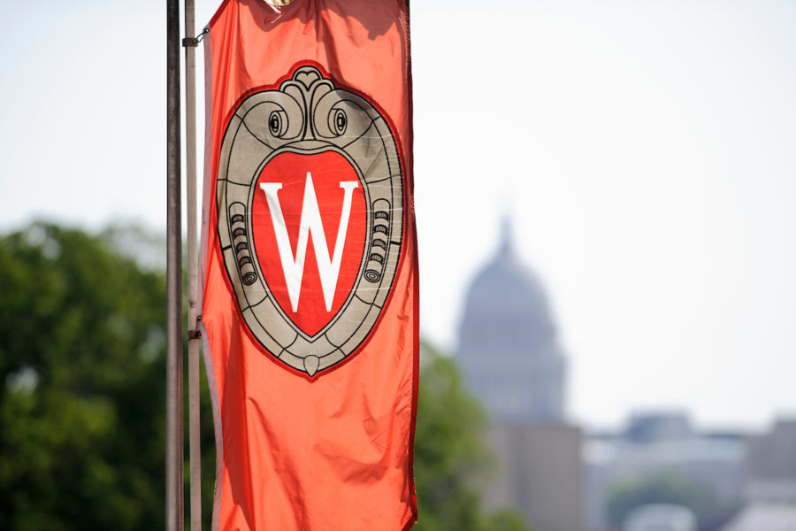 A W crest banner hanging on Bascom Hill at the University of Wisconsin-Madison is pictured in relation to an out-of-focus view of the Wisconsin State Capitol